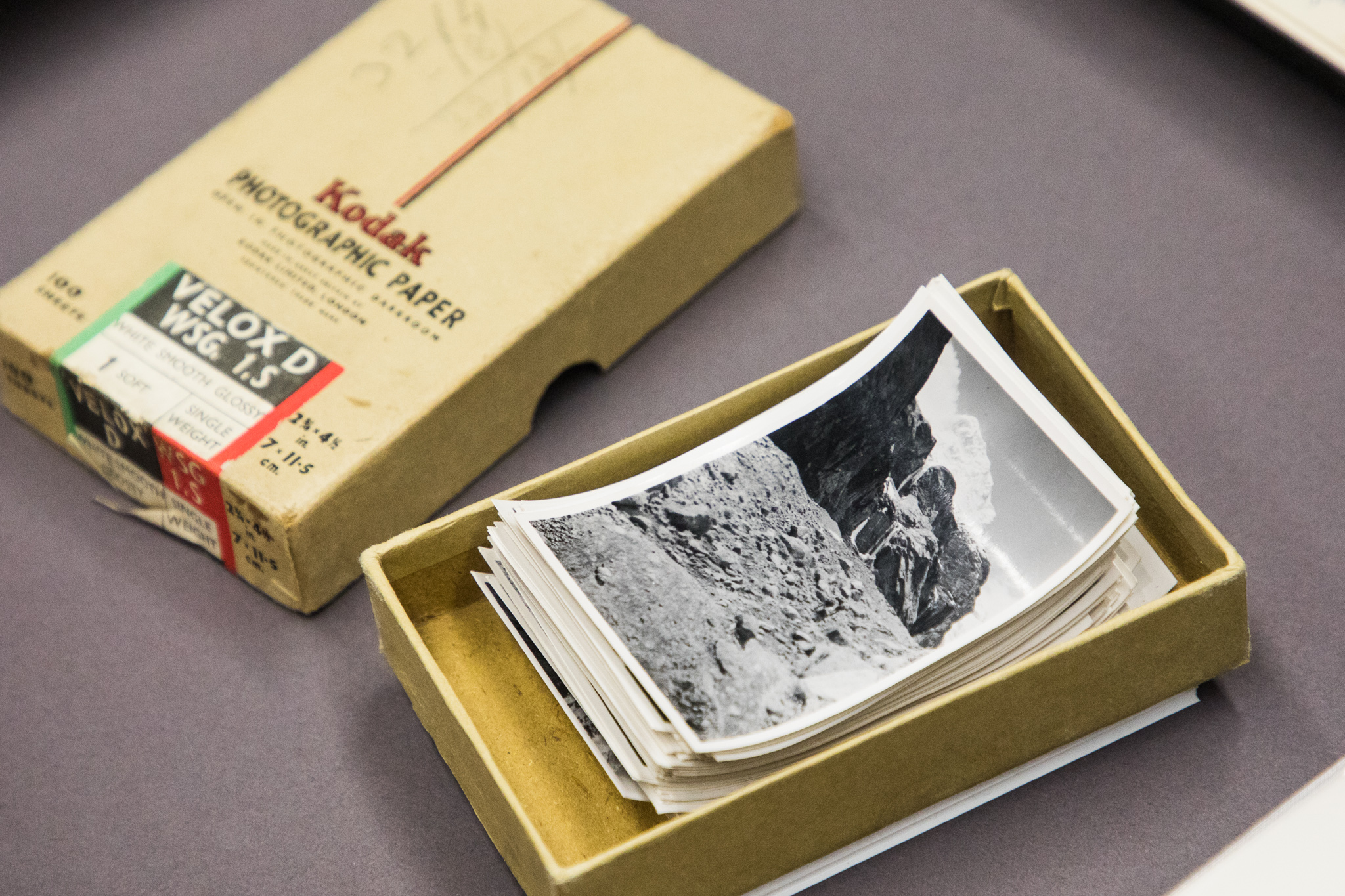 Shows a small box of black and white photographs.
