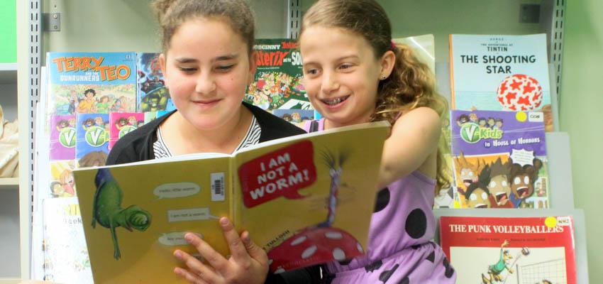 2 tweens enjoying sharing a book