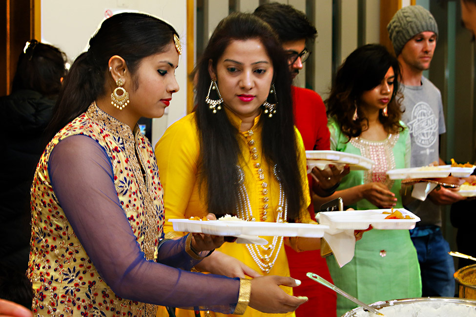 Diwali, Festival of Lights, Whangārei. In the foreground women are eating food prepared for the celebration. They are wearing brightly coloured clothing and elaborate jewellery.  [Diwali](/files/schools/hm52-diwali-english.mp3)