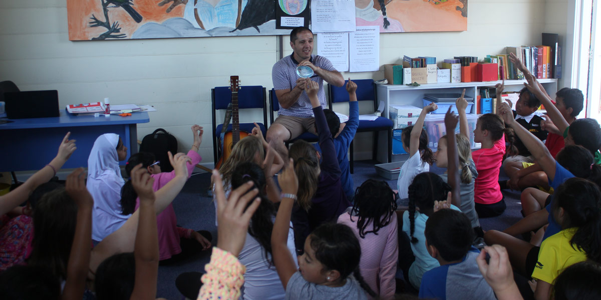 Primary school students sitting on the mat with their hands raised, as a teacher shows them what looks like a large paua shell
