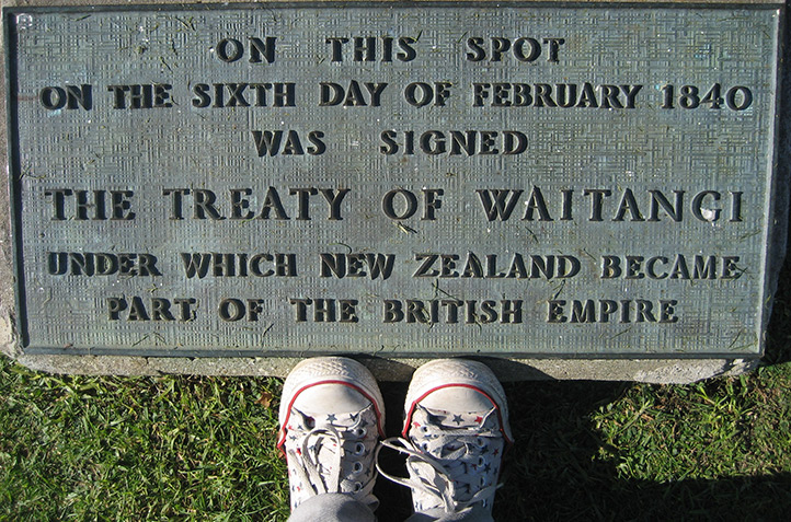 Sneakers of a young person standing next to a plaque that reads: 'On this spot on the sixth day of February 1840 was signed The Treaty of Waitangi under which New Zealand became part of the British Empire'