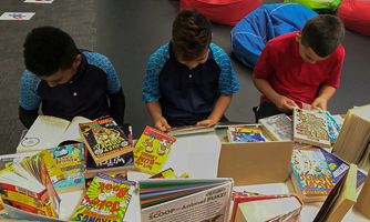 Three young boys selecting books to read.