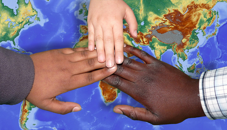 Children's hands overlapping on a world map