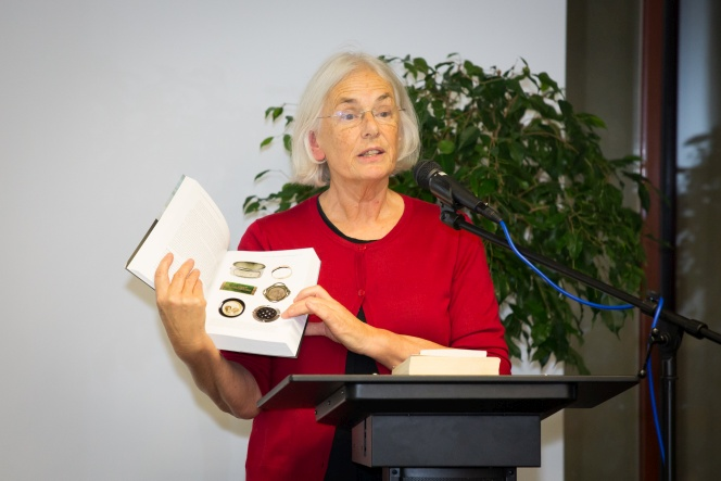 Bridget Williams speaking and showing one of her books.