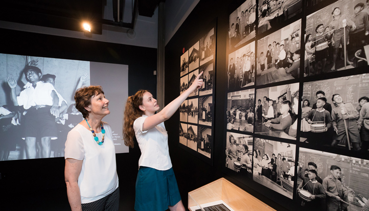 Student and adult looking at the Ans Westra images in the Pūkana exhibition at the National Library in Wellington