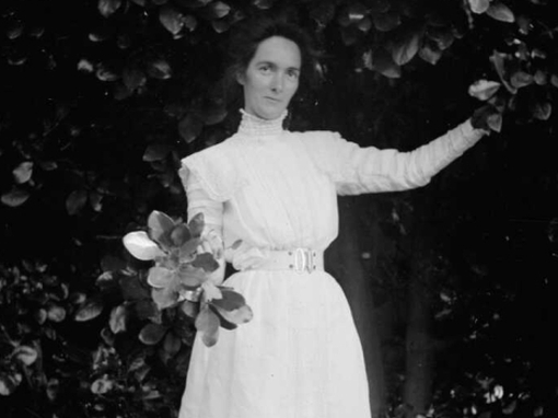 Black and white photo shows a woman holding a bunch of leaves wearing a white dress.