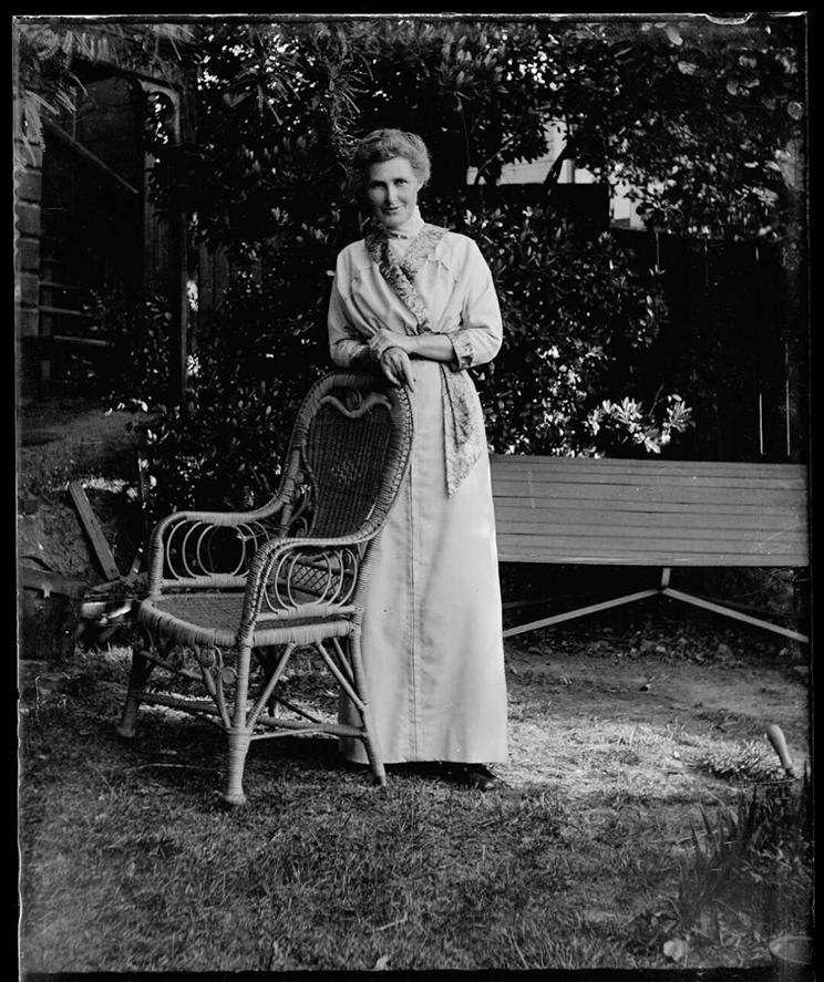 Woman leaning on the back of a cane chair in front of a garden bench.