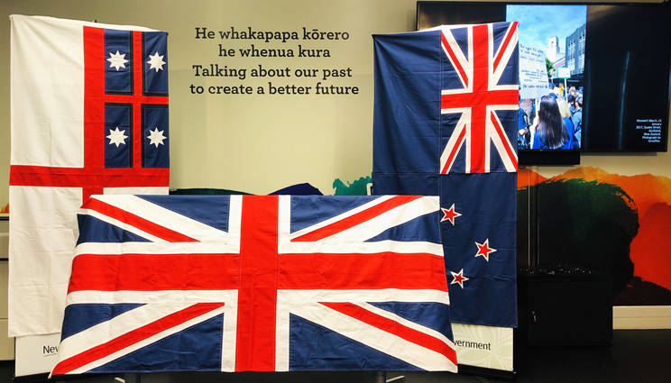 3 flags of Aotearoa New Zealand displayed in the He Tohu Tāmaki exhibition space in front of words:'He whakapapa kōrero he whenua kura. Talking about our past to create a better future'.