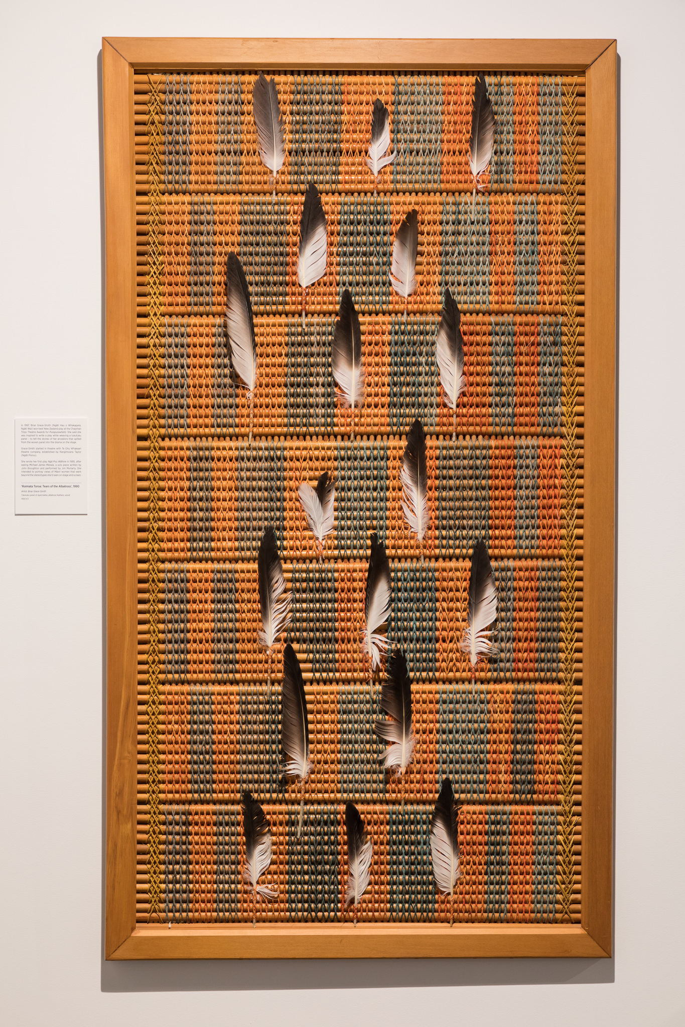 orange, brown and green woven panel with feathers on it.