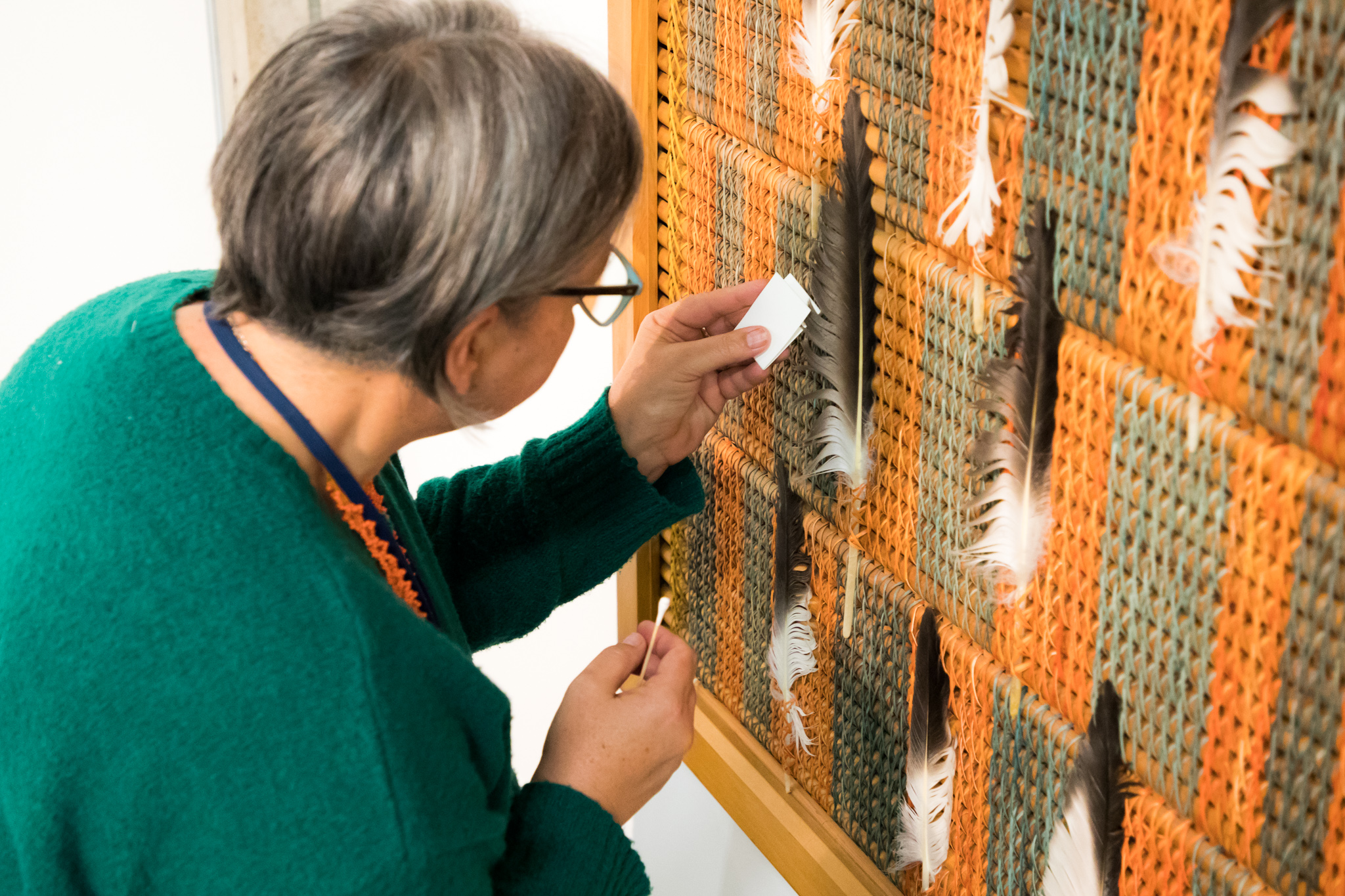 Woman looking closely at a feather on the panel.
