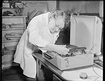 Woman in white coat moving the arm of a record player to start a record playing.