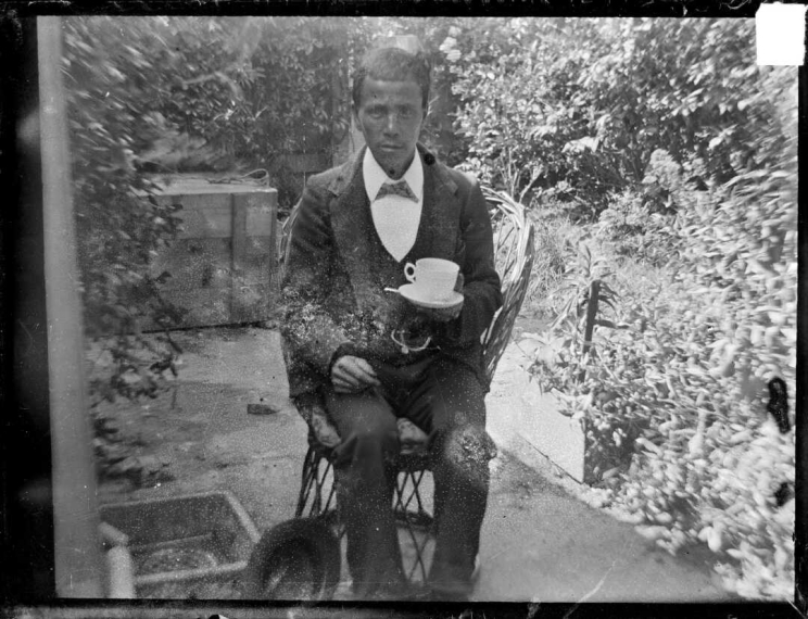 A man in formal dress is seated outdoors in a garden holding a cup of tea on a saucer.