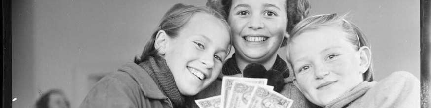 Three girls holding a fan of dollar notes they have saved.