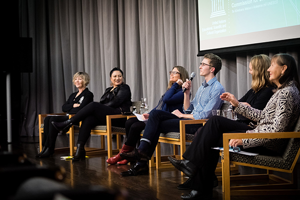People in a panel discussion looking at an audience.