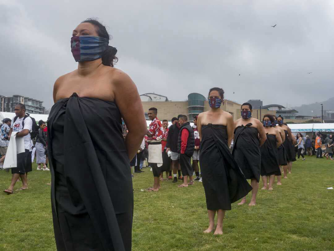 Women in a line wearing black wraps around their torsos, shoulders are bare. They have flags covering the lower part of their faces. Their hands are behind their backs.