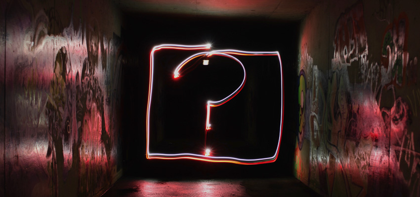 An illuminated square containing an illuminated question mark set in a dark tunnel.