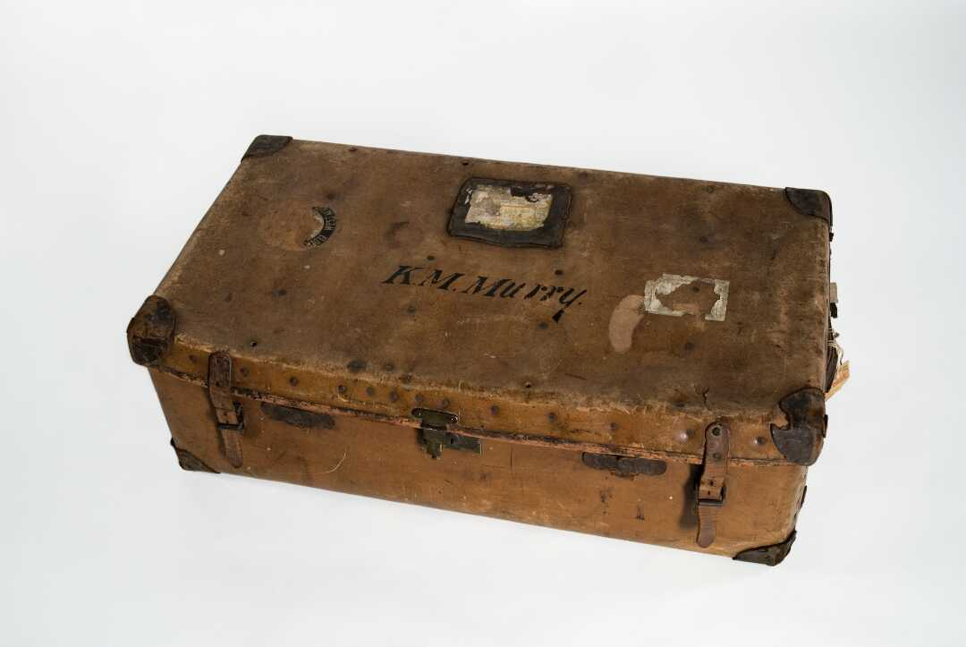 """A worn brown leather suitcase with the letters """"K.M. Murry"""" on the outside."""