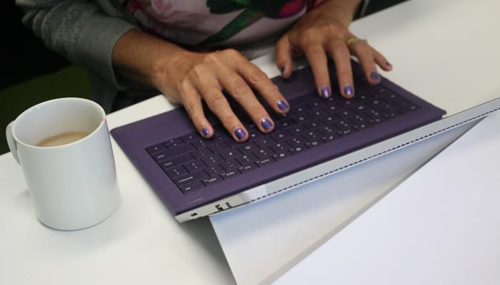 Person wearing purple nail polish typing on a purple keyboard