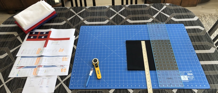 Technical drawings and fabric on a table with ruler, rotary cutting tool, and cutting mat