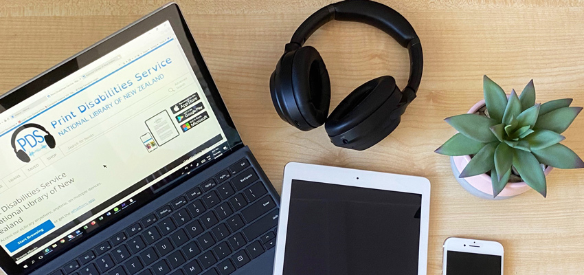 Laptop with Print Disabilities Service Wheelers platform on the screen alongside headphones and other digital devices