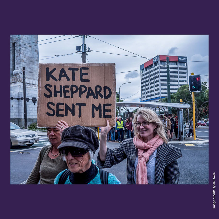 Front of curiosity card CC0007 with an image of women marching in Wellington and holding a sign with the words 'KATE SHEPPARD SENT ME'.