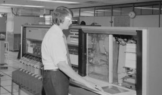 Man operating large computer in 1975.