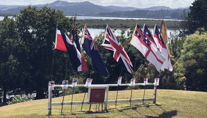 8 flags on display in front of harbour background