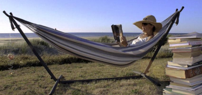 A woman reading in a hammock by a beach.