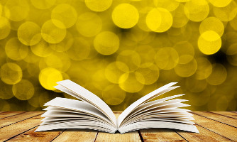 Open book with yellow lights in background.