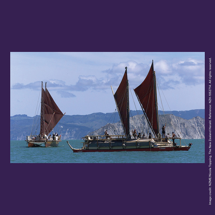 Front of curiosity card TMCC2 with image of waka hourua (double-hulled canoe) Te Aurere being greeted in Tūranganui-a-Kiwa / Poverty Bay.