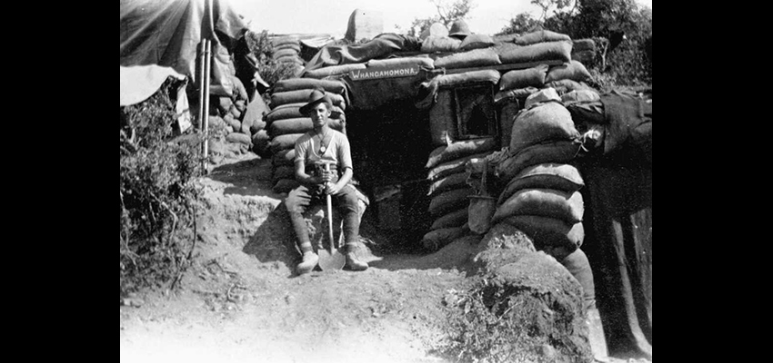 An unidentified New Zealand outside his dug-out in a trench during World War I. A sign above the door reads 'Whangamomona' which may be where the soldier hails from.