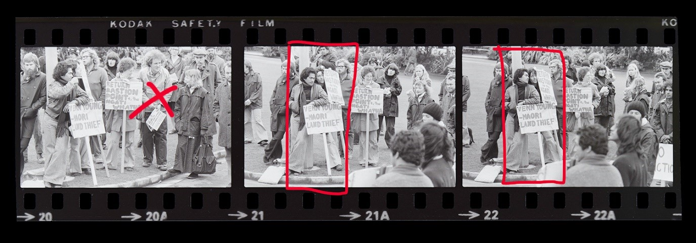 A strip of film showing three frames, each with the same scene from a protest march where attendees can be seen holding signage. There are red, hand-drawn marks on each frame indicating where the image was cropped.