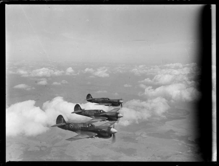 Three Kittyhawk propeller planes flying in formation beside one another and above the clouds.