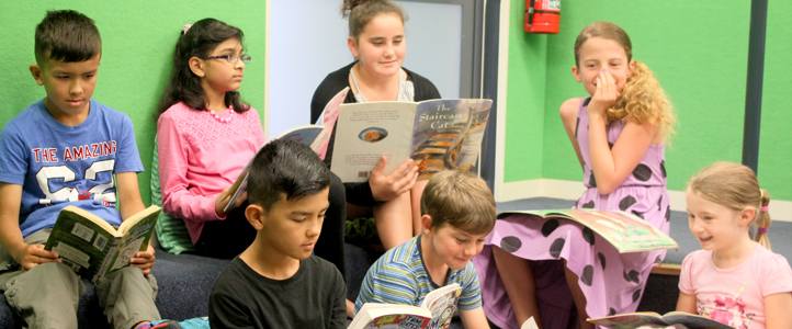 Class of students reading books in the school library