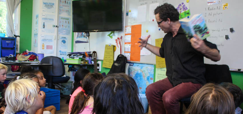 Teacher reading aloud to his class.