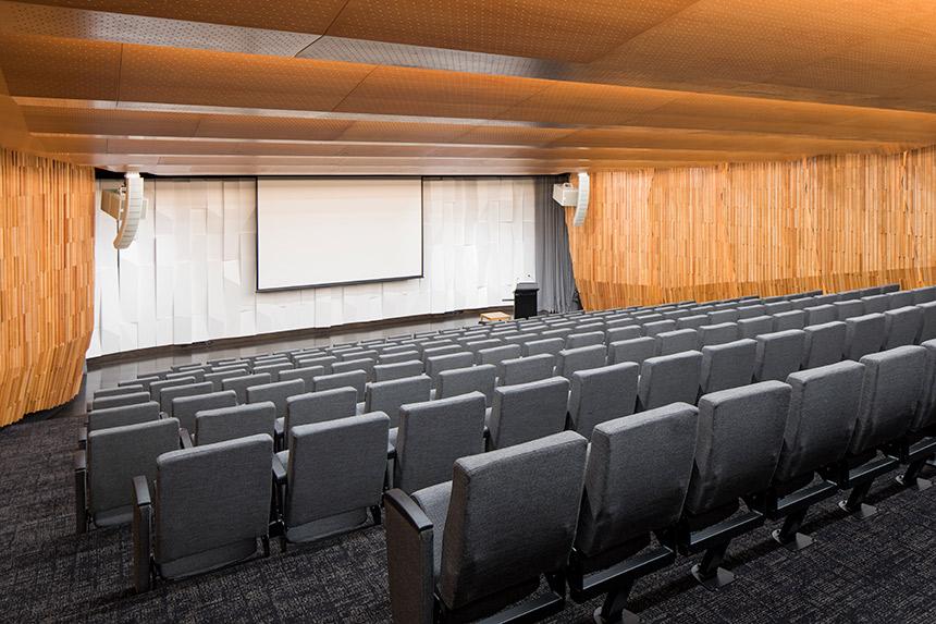 Empty auditorium showing seats, podium, and beautiful wood panelling.