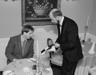 Philip Temple, Orsini's proprietor, presenting a bottle of wine to a customer.