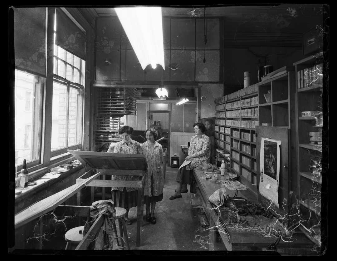 Shows three women in a workroom, most likely colourising b&w photographs.