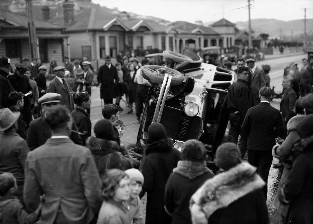 Shows a scene in black and white with a crowd surrounding a car that has flipped onto its side in the middle of the street.