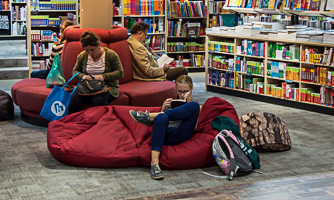 Young people in a school library reading books.