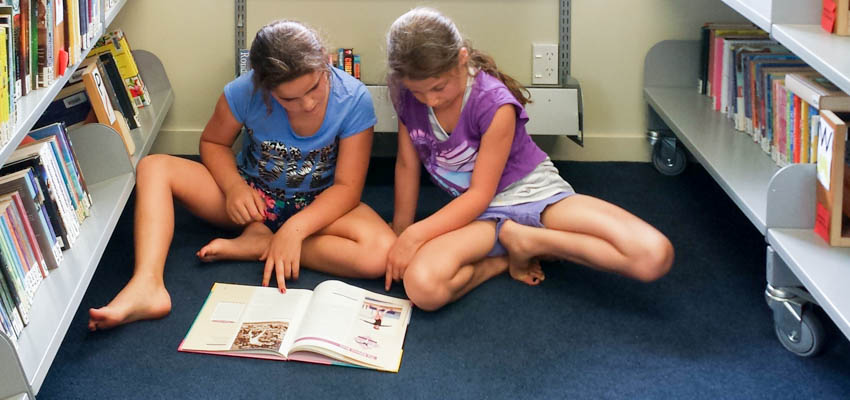 2 tweens reading a book in the school library