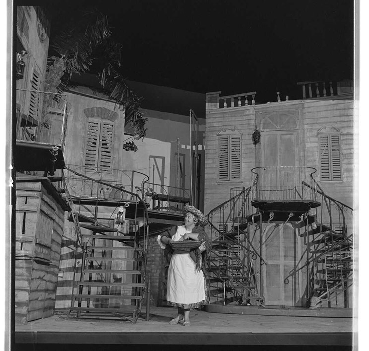 Woman on a stage set holding a basket with strawberries.