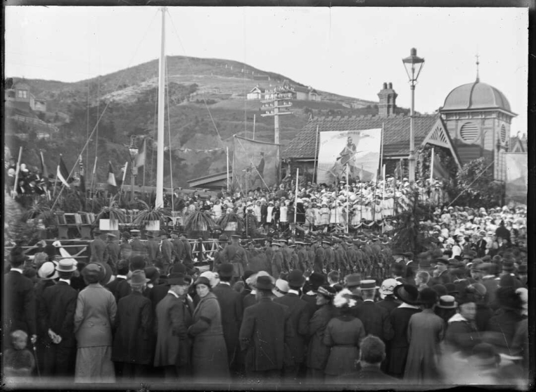 Shows a crowd, flagpole and banners next to the Petone Railway Station.