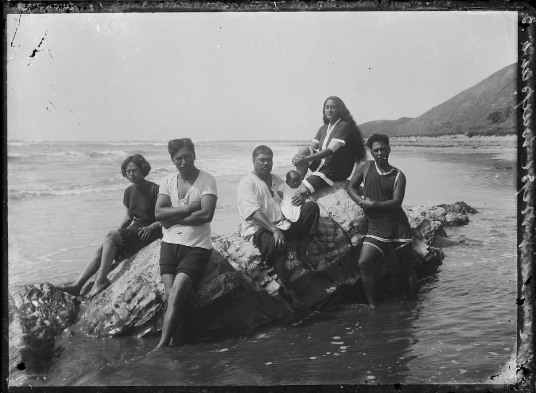 Shows a family including small baby sitting atop rocks at the shore, some members are standing in the water.