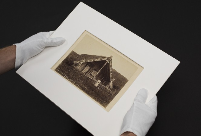 Gloved hands holding a photo of the whare belonging to King Tawhiao at Te Kuiti.