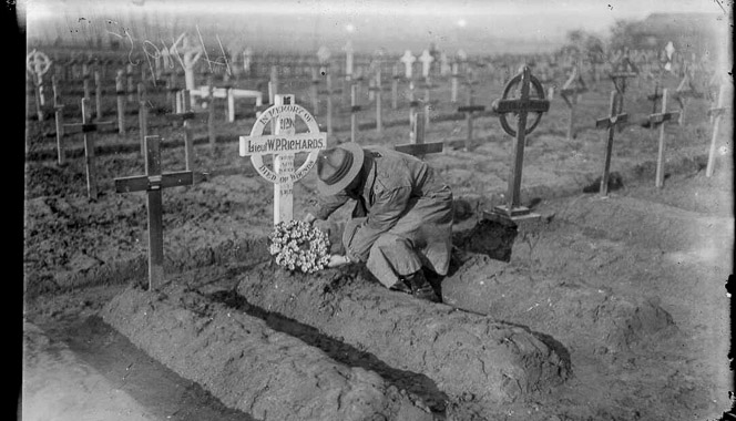 Soldier laying a wreath on a recently filled grave in a cemetery.