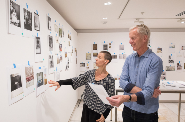 Fiona Oliver and Peter Ireland in the planning stages of an exhibition in a room with images of collection items on all the walls.