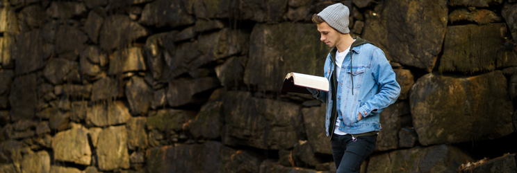 A teenager in jean jacket and hat standing reading a book outside in front of a rock wall