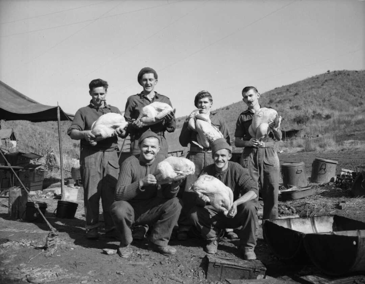 A group of six men posing for photo while holding raw turkeys ready for cooking.