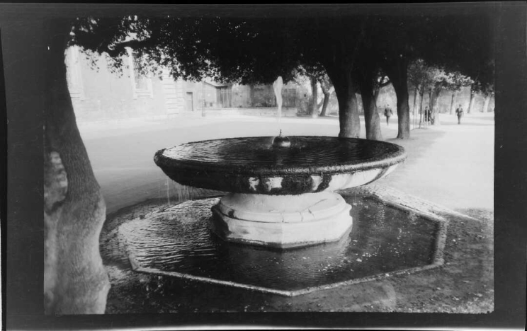 A fountain in the shape of a large, raised bowl is filled with water that is dripping over the edge into a larger pool that is octagon-shaped nearly at ground level.